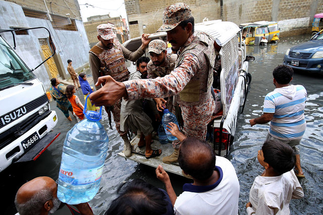 Pakistani Rangers distribute food to people affected by monsoon rains in Karachi, Pakistan, 26 August 2020. Sindh provincial government declared an emergency after heavy monsoon rain flooded several areas of Karachi causing traffic jams and power outages. (Photo by Shahzaib Akber/EPA/EFE/Rex Features/Shutterstock)