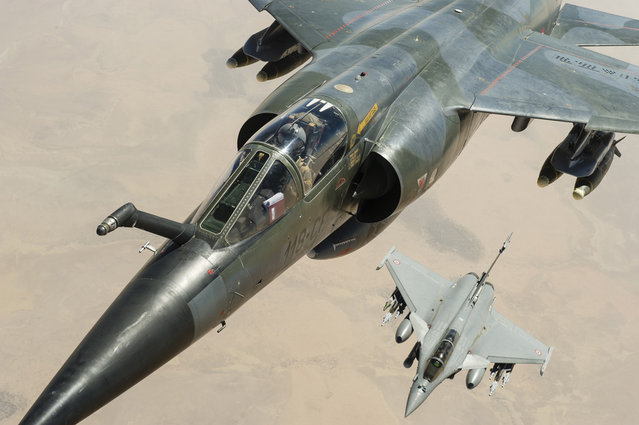 A French Mirage F1CR (top) and a Rafale jetfighter fly over Mali, on February 4, 2013. (Photo by Anthony Jeuland/AP Photo/ECPAD/French Air Force/The Atlantic)