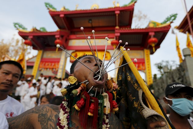 A devotee of the Chinese Jui Tui shrine walk with spikes pierced on his cheeks during a procession celebrating the annual vegetarian festival in Phuket, Thailand October 19, 2015. (Photo by Jorge Silva/Reuters)