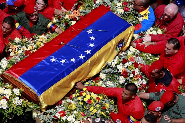 The flag-draped coffin containing the body of Venezuela's late President Hugo Chavez is taken to the military academy where it will remain until his funeral, March 6, 2013. Seven days of mourning were declared, all schools were suspended for the week and friendly heads of state were expected for an elaborate funeral Friday. (Photo by Ricardo Mazalan/Associated Press)