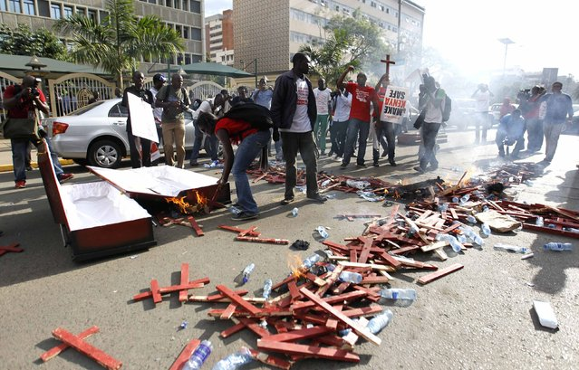Protesters burn wooden crosses, symbolising people killed in a series of attacks, and coffins during the #OccupyHarambeeAve demonstration in Kenya's capital Nairobi November 25, 2014. (Photo by Thomas Mukoya/Reuters)
