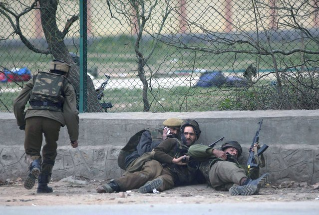 Indian policemen take cover during a gunbattle in Srinagar, India, Wednesday, March 13, 2013. A team of militants stormed a paramilitary camp Wednesday morning in the capital of Indian-controlled Kashmir, leaving five soldiers and two militants dead and 10 more people wounded, a police official said. (Photo by Dar Yasin/AP Photo)