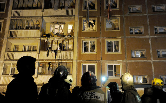 Rescuers look at an apartment block damaged by a gas explosion in St. Petersburg late on March 22, 2013. Eight people were injured in the blast and one women died later in hospital, the Russian media reported. (Photo by Olga Maltseva/AFP Photo)