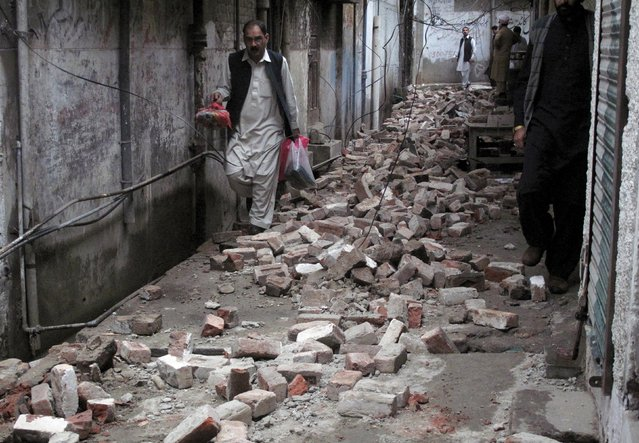 A man with his belongings walks past the rubble of a house after it was damaged by an earthquake in Mingora, Swat, Pakistan October 26, 2015. (Photo by Hazrat Ali Bacha/Reuters)