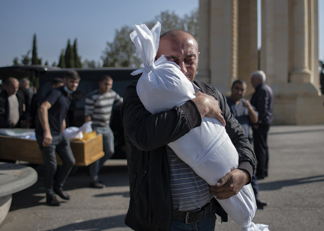 Timur Haligov, an Azerbaijani Turkish father embraces the body of his 10-month-old baby girl, Narin, who was killed by overnight shelling by Armenian forces. during a funeral ceremony, in Ganja, Azerbaijan, Saturday, October 17, 2020. Azerbaijan has accused Armenia of striking its second-largest city with a ballistic missile that killed at least 13 civilians and wounded 50 others in a new escalation of their conflict over Nagorno-Karabakh. (Photo by Can Erok/DHA via AP Photo)