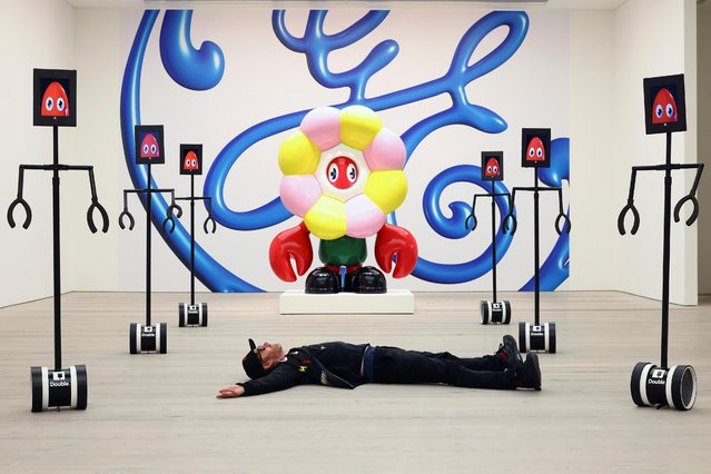Philip Colbert poses for a photograph with robots that allow viewers to interactively engage with his Lobsteropolis exhibition at a preview event at the Saatchi Gallery in London, Britain, October 28, 2020. (Photo by Simon Dawson/Reuters)