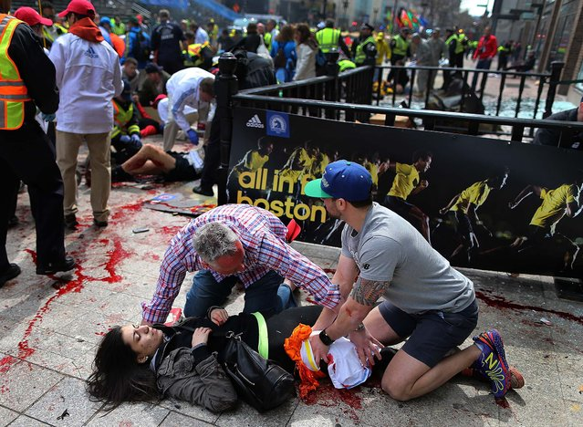 An injured woman is tended to at the scene of the first explosion on Boylston Street. (Photo by John Tlumacki/The Boston Globe)