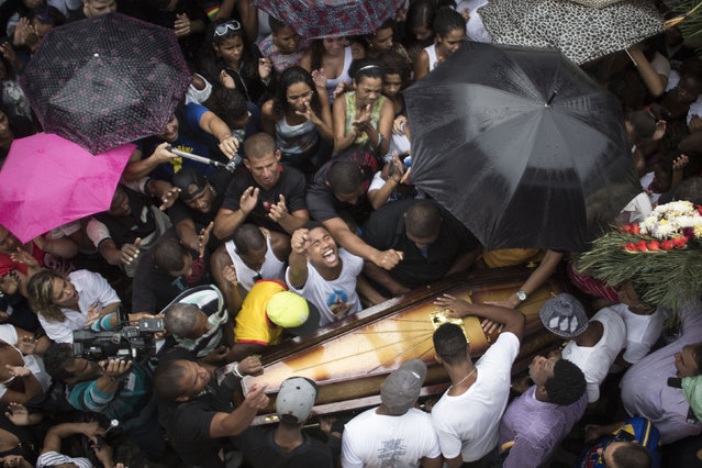 In this April 24, 2014 file photo, the relatives and friends of Douglas Rafael da Silva Pereira grieve around his coffin as they bury him in Rio de Janeiro, Brazil. A protest followed the burial of Silva Pereira, whose shooting death sparked clashes between police and residents. (Photo by Felipe Dana/AP Photo)