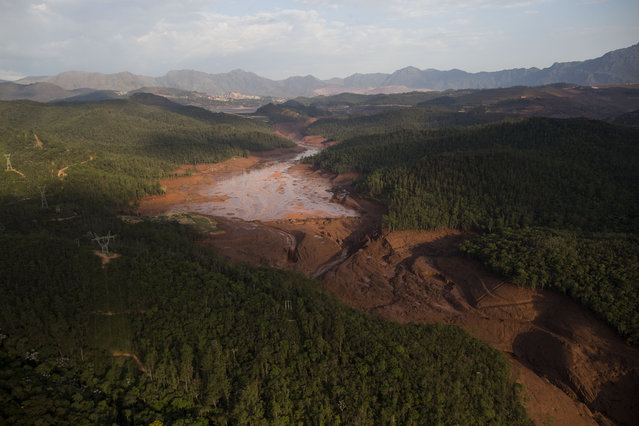 Aerial view of the small town of Bento Rodrigues after a dam burst on Thursday in Minas Gerais state, Brazil, Friday, November 6, 2015. Brazilian rescuers searched feverishly Friday for possible survivors after two dams burst at an iron ore mine in a southeastern mountainous area. (Photo by Felipe Dana/AP Photo)