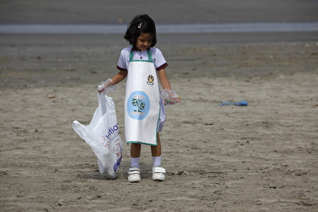 A schoolgirl collects rubbish from Karachi's Clifton beach early morning April 22, 2013, during a cleaning campaign as part of the commemoration of Earth Day. (Photo by Akhtar Soomro/Reuters)