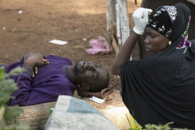 Adama Tarawallie reacts near her husband Ibrahim, 31, a suspected Ebola victim, as they wait to be transported from Devils Hole North, west of Freetown, Sierra Leone, December 17, 2014. The death toll in the Ebola epidemic has risen to 6,915 out of 18,603 cases as of December 14, the World Health Organization (WHO) said on Wednesday. (Photo by Baz Ratner/Reuters)