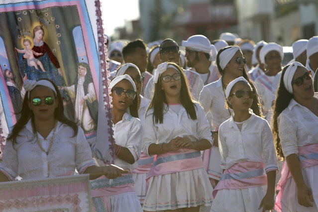 In this October 9, 2016 photo, girls sing as they carry an image of Our Lady of Rosary during the annual Afro-Christian Congada celebration in Catalao, Goias state, Brazil. The group's leader sings a verse, and members repeat, making references to Brazil's history of slavery as well as Catholic Church and African traditions, a testament to the mixing of cultures, religions and races in Latin America's largest nation. (Photo by Eraldo Peres/AP Photo)