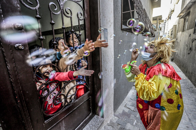A Palestinian clown wearing a face mask while entertaining children at their home during the lockdown after the outbreak of the COVID-19 pandemic in Jabalia Refugee Camp in northern Gaza Strip on November 18, 2020. (Photo by Mahmoud Issa/Quds Net News/ZUMA Wire/Rex Features/Shutterstock)
