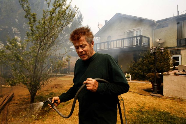 Richard Jenson tries to protect his home from the advancing wildfire in the mountains above Malibu on Friday. (Photo by Al Seib/Los Angeles Times)