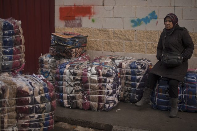 A women porter rests on bundles destined for transport across the El Tarajal boarder separating Morocco and Spain's North African enclave of Ceuta, in Ceuta on December 4, 2014. (Photo by Jorge Guerrero/AFP Photo)
