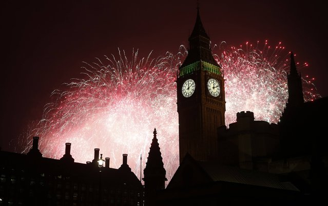 Fireworks explode behind the Houses of Parliament and Big Ben on the River Thames during New Year celebrations in London January 1, 2015. (Photo by Suzanne Plunkett/Reuters)