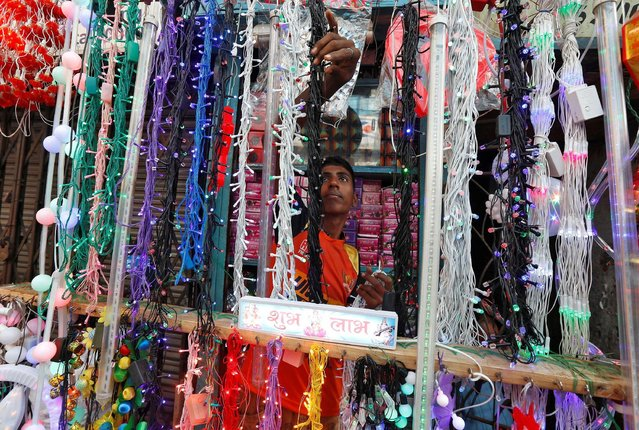 A shopkeeper hangs lights for sale, which are used to decorate temples and homes during the Hindu festival of Diwali, in Kolkata, India October 18, 2016. (Photo by Rupak De Chowdhuri/Reuters)