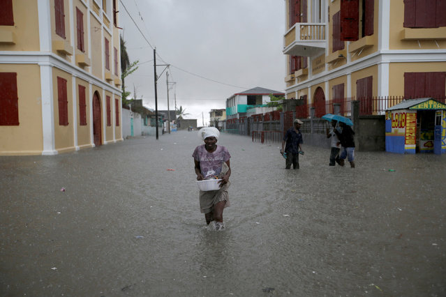 A woman walks in a flooded street during rain after Hurricane Matthew in Les Cayes, Haiti, October 21, 2016. (Photo by Andres Martinez Casares/Reuters)