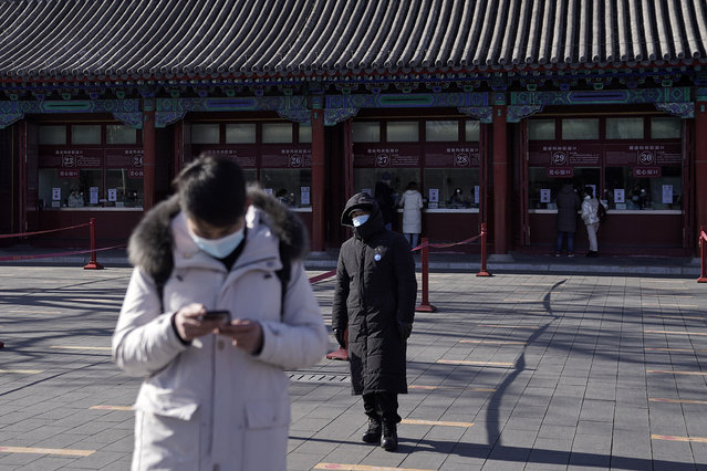 A man wearing a face mask to help curb the spread of the coronavirus browses his smartphone as a masked security guard stands near the quiet ticket counters at the Forbidden City in Beijing, Sunday, January 10, 2021. More than 360 people have tested positive in a growing COVID-19 outbreak south of Beijing in neighboring Hebei province. (Photo by Andy Wong/AP Photo)