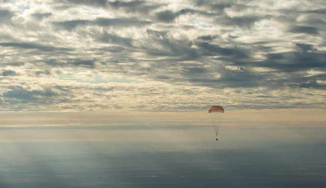 The Soyuz MS-01 spacecraft lands with Expedition 49 crew members NASA astronaut Kate Rubins, Russian cosmonaut Anatoly Ivanishin of Roscosmos, and astronaut Takuya Onishi of the Japan Aerospace Exploration Agency (JAXA), near the town of Zhezkazgan, Kazakhstan on Sunday, October 30, 2016. (Photo by Bill Ingalls/NASA via AP Photo)