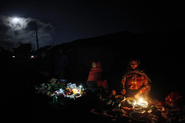 Nepalese roadside vendors wait for the customer to sell the item used for ritual during the first day Swasthani Bratakatha festival in Sankhu, on the outskirts of Katmandu, Monday, January 5, 2015. During this month-long festival, devotees recite Holy Scriptures dedicated to Hindu goddess Swasthani and Lord Shiva. (Photo by Niranjan Shrestha/AP Photo)