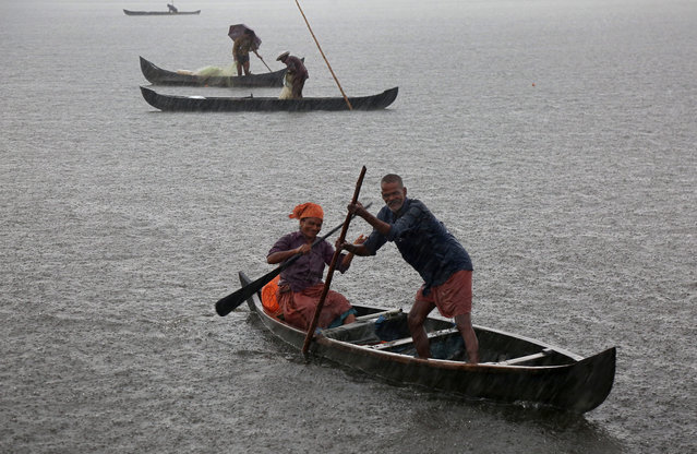 A fisherman and his wife row their boat in a fishing farm as it rains heavily on the outskirts of Kochi, India, May 29, 2018. (Photo by Sivaram V/Reuters)
