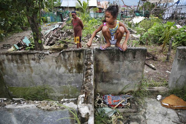 A girls stands in ruins above human remains and a shirt found with it in the coastal part of Tacloban, that was destroyed by Typhoon Haiyan, January 16, 2015. Local residents said they found human remains in the mud among ruins of their wrecked fishing village and assume it is a typhoon victim. (Photo by Damir Sagolj/Reuters)