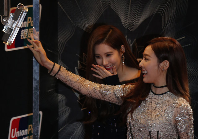 South Korean actress singers Tiffany (R) and Seohyun react in front of an official camera on the red carpet during 2015 Mnet Asian Music Awards (MAMA) in Hong Kong, China December 2, 2015. (Photo by Bobby Yip/Reuters)