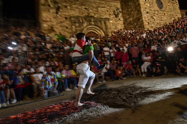 A man carries a young boy while walking on the burning embers during the night of San Juan in San Pedro Manrique, northern Spain, Sunday, June 24, 2018. The night of San Juan, which welcomes the summer season, is an ancient tradition celebrated every year in various towns in Spain. (Photo by Alvaro Barrientos/AP Photo)