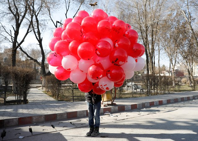 An Afghan boy holds balloons for sale during a Valentine's Day celebration in Kabul, Afghanistan on February 14, 2021. (Photo by Mohammad Ismail/Reuters)