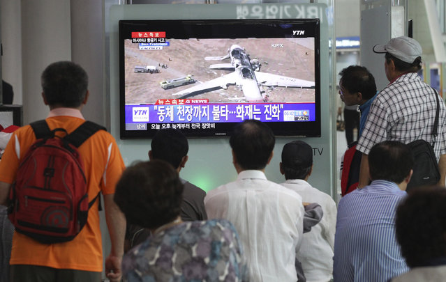 """People watch a news program reporting about Asiana Airlines flight 214 which took off from Seoul and crashed while landing at San Francisco International Airport, at Seoul Railway Station in Seoul, South Korea, Sunday, July 7, 2013. The writing on the screen reads """"Fire on the ceiling of the airplane"""". (Photo by Ahn Young-joon/AP Photo)"""