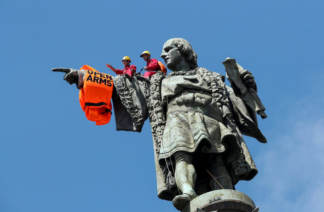 Activists from the Spanish Proactiva Open Arms charity place a life jacket on the Christopher Columbus statue after the Open Arms rescue boat arrived at a port in Barcelona, Spain, carrying migrants rescued off Libya, July 4, 2018. (Photo by Albert Gea/Reuters)