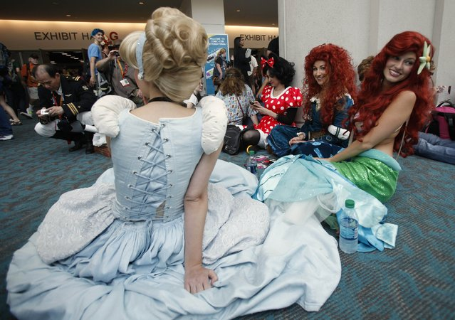 Girls wearing Cinderella (L), Ariel the Little Mermaid (R) and Minnie Mouse (3rd R) costumes sit on the floor during the Comic Con International convention in San Diego, California July 13, 2012. (Photo by Mario Anzuoni/Reuters)