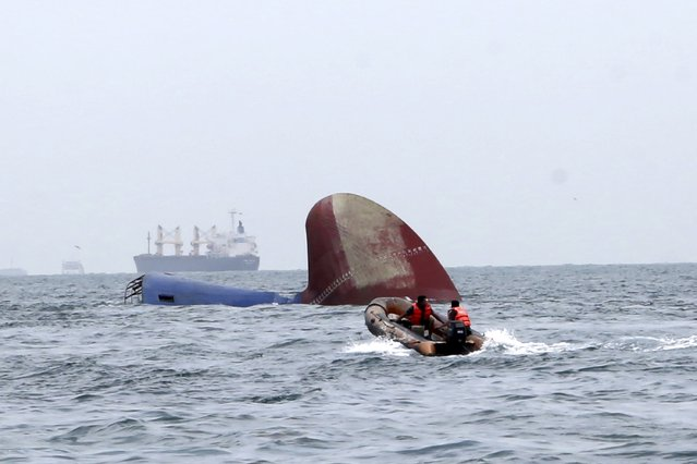 An Indonesia rescue team approaches the sunken Antigua and Barbuda flagged freighter MV Thorco Cloud which sank after colliding with a tanker the night before, in the Singapore Strait off the Indonesian island of Batam December 17, 2015 in this photo taken by Antara Foto. (Photo by M.N. Kanwa/Reuters/Antara Foto)