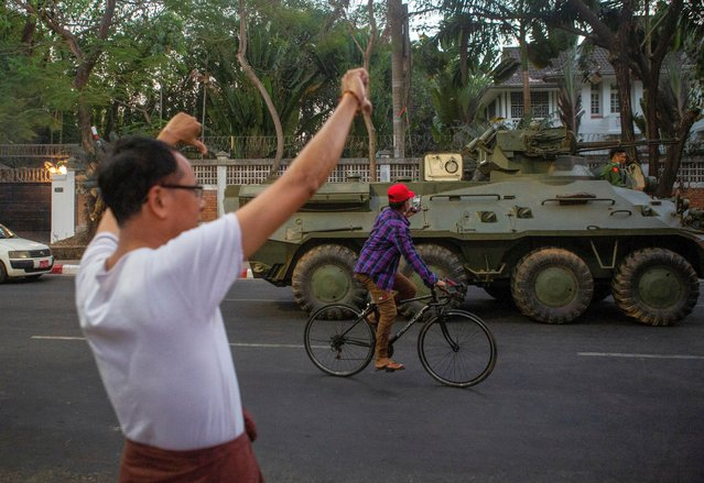 A man on a bike takes a picture of an armoured vehicle riding on a street during a protest against the military coup, in Yangon, Myanmar, February 14, 2021. (Photo by Reuters/Stringer)