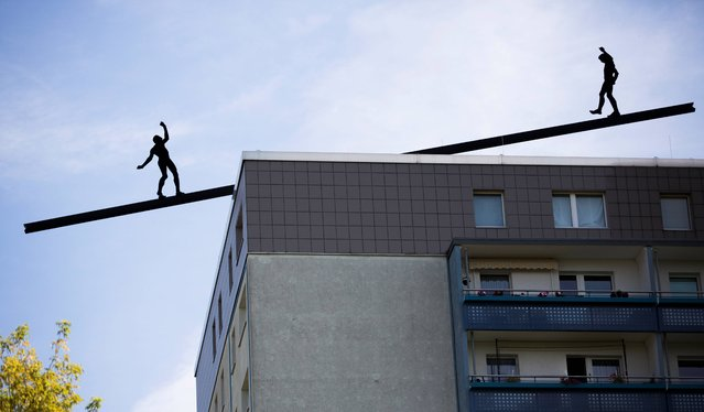 "Two aluminum figures of an installation are silhouetted on a rooftop in Berlin, Germany, Wednesday, July 24, 2013. The installation of German artist Hubertus von der Goltz is called ""Encounters and Positions"". (Photo by Gero Breloer/AP Photo)"