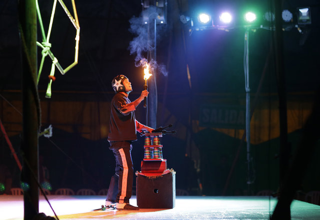 In this July 20, 2018 photo, juggler Alfredo Cordova performs with fire at the International Circus set up in the shantytown of Pro on the outskirts of in Lima, Peru. The mom-and-pop style spectacle is one of about a hundred remaining circuses that manage to eke out a living in an age of viral internet videos and cellphones. (Photo by Martin Mejia/AP Photo)