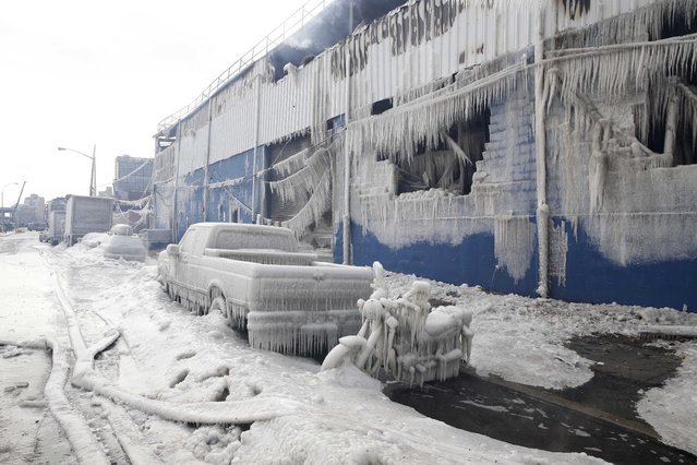 Vehicles and a building are covered with ice as firefighters work to keep a warehouse fire down in the Brooklyn borough of New York, Sunday, February 1, 2015. Firefighters are still dousing the massive warehouse fire that started Saturday. Fire Department officials say air quality in the Williamsburg section has been compromised by the blaze that left one person injured from smoke inhalation. (Photo by Seth Wenig/AP Photo)