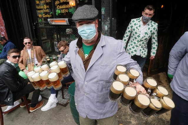 A worker, wearing a protective mask, carries beers to customers at McSorley's Old Ale House on St. Patrick's Day, amid the coronavirus disease (COVID-19) pandemic, in New York City, New York, U.S., March 17, 2021. (Photo by Carlo Allegri/Reuters)