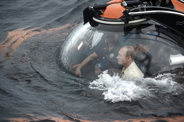 Russian President Vladimir Putin (front) is seen inside a research bathyscaphe while submerging into the waters of the Black Sea as he takes part in an expedition near Sevastopol, Crimea, August 18, 2015. (Photo by Alexei Nikolsky/Reuters/RIA Novosti/Kremlin)