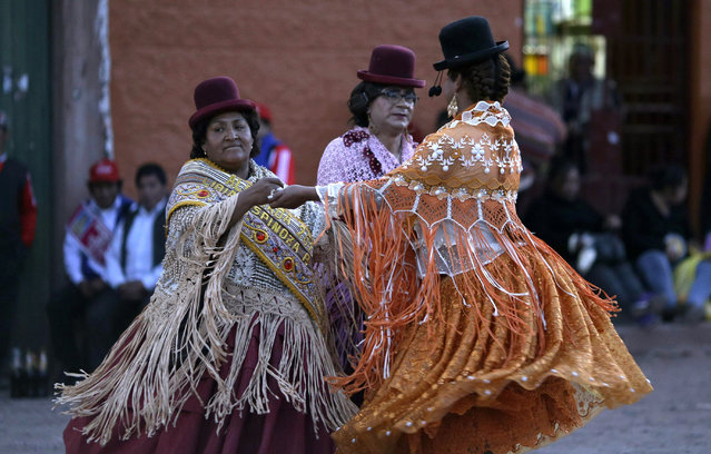 In this Sunday, August 5, 2018 photo, steward Libia Espinoza, left, dances with transgenders Coco and Jessi during festivities honoring Our Lady of Copacabana, in Cuzco, Peru. Espinoza is credited with the first Cuzco celebration venerating the Bolivian virgin, who she believes cured her of her kidney problems. (Photo by Martin Mejia/AP Photo)