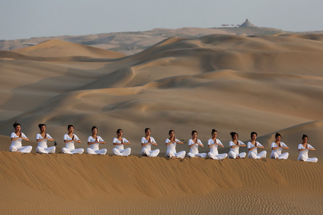 Dancers perform yoga on the dunes of Xiangshawan Desert, also called Sounding Sand Desert on July 20, 2013 in Ordos of Inner Mongolia Autonomous Region, China. (Photo by Feng Li/Getty Images)