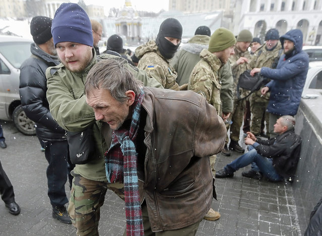 A patrol of Ukrainian policemen and volunteer battalions members arrest men, who are suspected of terrorism on the Independence square in Kiev, Ukraine, 09 February 2015. (Photo by Sergey Dolzhenko/EPA)