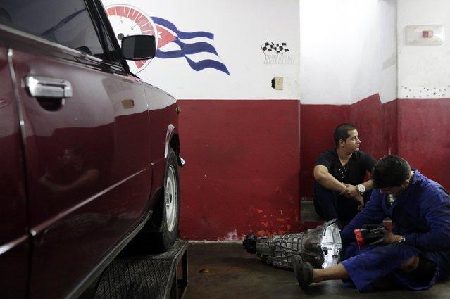 Mechanics work on a piece of a Lada in a car shop in Havana February 9, 2015. (Photo by Enrique De La Osa/Reuters)