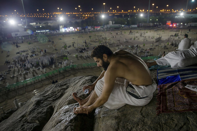 A Muslim hajji pilgrim washes, performing ablution before offering early morning prayers at Jabal Al Rahma holy mountain, or the mountain of forgiveness, at Arafat for the annual hajj pilgrimage, outside the holy city of Mecca, Saudi Arabia, Monday, August 20, 2018. More than 2 million Muslims have begun the annual hajj pilgrimage, one of the five pillars of Islam which is required of all able-bodied Muslims once in their lifetime. (Photo by Dar Yasin/AP Photo)