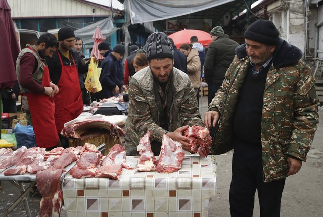 An Ethnic Armenian man chooses meat at the market in Stepanakert, the capital of the separatist region of Nagorno-Karabakh, on Saturday, November 21, 2020. Ethnic Armenians return to a normal life after a Russia-brokered cease-fire was signed between Armenia and Azerbaijan. (Photo by Sergei Grits/AP Photo)