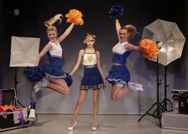 Dancers in cheerleader costumes perform as they pose for the photographers next to a wax figure of US singer Taylor Swift during a photo call in central London Tuesday, February 10, 2015. The new wax figure was unveiled at the Madame Tussauds London attraction. (Photo by Lefteris Pitarakis/AP Photo)