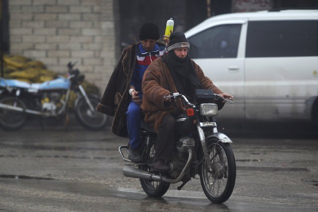 Men ride on a motorbike as one of them carries his serum bag in the rebel-controlled area of Maaret al-Numan town in Idlib province, Syria, January 4, 2016. (Photo by Khalil Ashawi/Reuters)