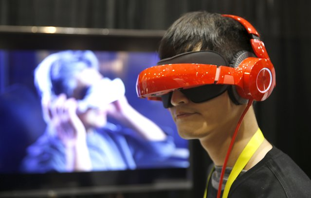 """Eric Yu of Royole models the company's foldable Smart Mobile Theater system during """"CES Unveiled,"""" a preview event of the 2016 International CES trade show, in Las Vegas, Nevada January 4, 2016. The $700.00 system has noise-canceling headphones and a viewing system that is vision correctable so you don't need to wear your glasses, Yu said. (Photo by Steve Marcus/Reuters)"""