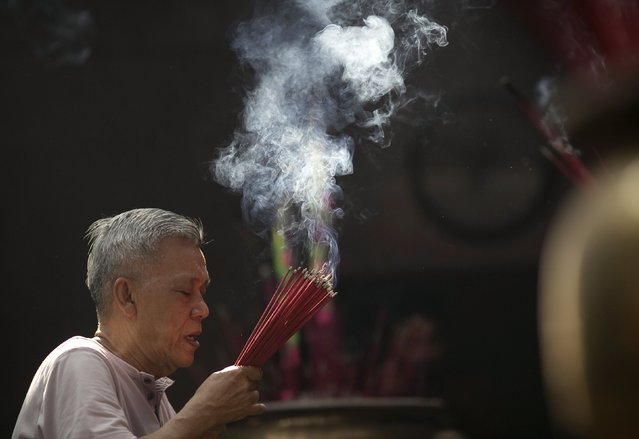 A man prays at Petak Sembilan Chinese Buddhist temple on the eve of Chinese Lunar New Year celebrations, at in Jakarta, February 18, 2015. (Photo by Darren Whiteside/Reuters)